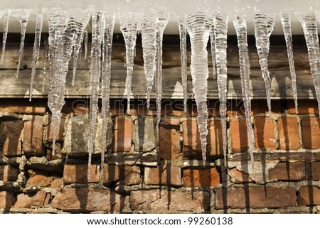 Ice icicles against a brick wall