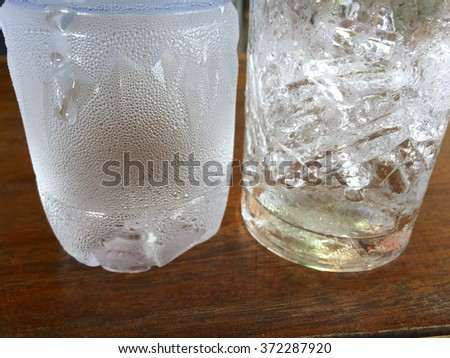 Ice in glass. Dew on plastic bottle. Clear glass on wood table. Ice in glass and plastic bottle. Drink glass. Dew on glass. Clear water. Ice and water. Ice and plastic bottle. Soda and glass. - stock photo