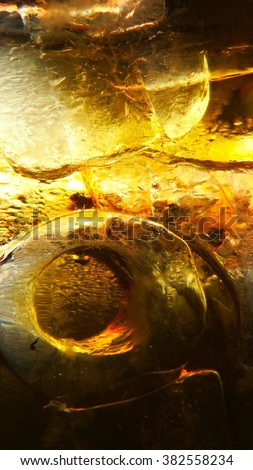 Ice in the glass and orange yellow beer droplets, abstract background - stock photo