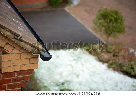Ice in the guttering and snow on the front grass - stock photo