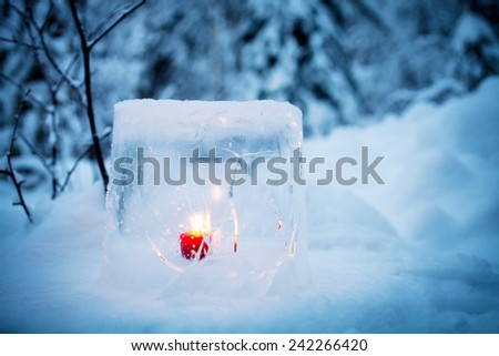 Ice lantern with red candle burning inside - stock photo