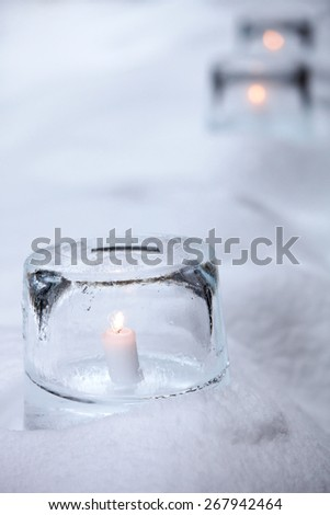 Ice lantern with white candle burning inside - stock photo