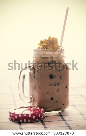 Ice latte with whipped cream in retro mug. Processed vintage filtered. - stock photo
