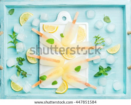 Ice lolly with lemon slices, fresh mint leaves and ice cubes on white ceramic board over blue Turquoise tray, top view, horizontal composition - stock photo