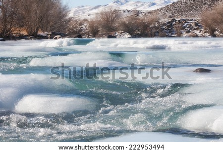 Ice on mountain river in winter - stock photo