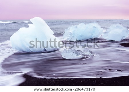 Ice on the black beach with the slow flow of wave at Jokulsarlon, Iceland - stock photo