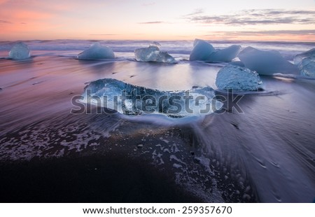 Ice on the black volcabic sand beach in Iceland - stock photo