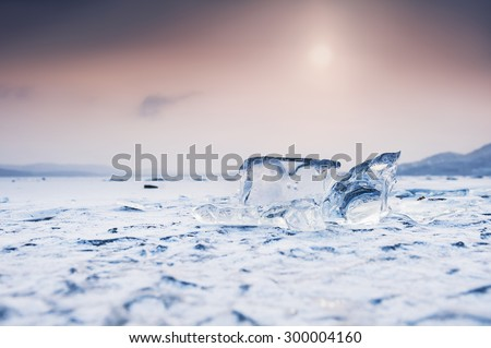 Ice on the frozen lake. Beautiful winter landscape at sunset. Small depth of field - stock photo