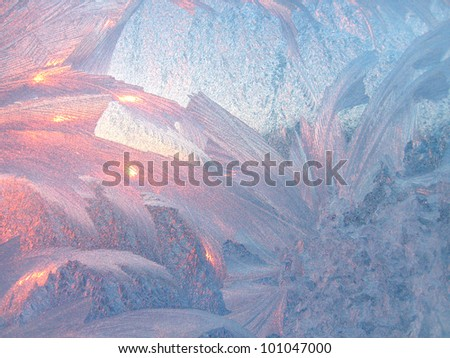 ice patterns and morning sunlight on winter glass - stock photo