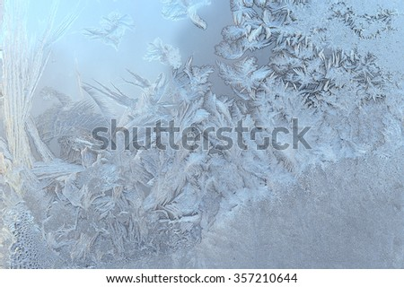 Ice patterns on glass in winter against the blue sky
