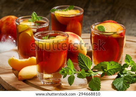 Ice Peach Tea with pieces of fruit, ice and mint on a wooden board, selective focus