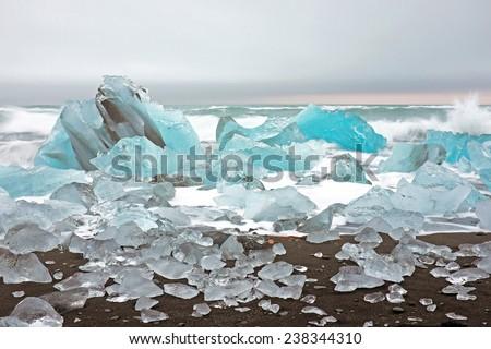 Ice rocks on a black sand beach in Iceland - stock photo