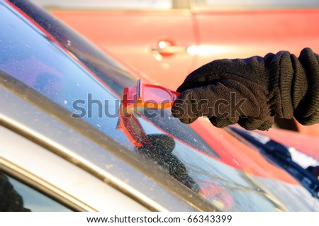 Ice scraping - removing snow and ice from car - stock photo