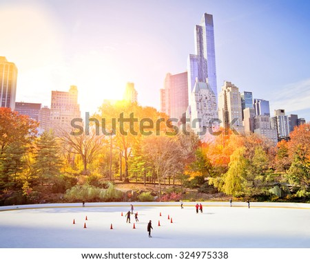 Ice skaters having fun in New York Central Park in fall with sun flare - stock photo