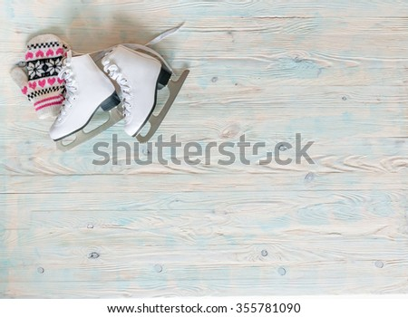 ice skates with mitten on wooden background with text space top view - stock photo
