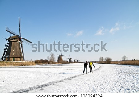 Ice skating at Kinderdijk in the winter in the Netherlands - stock photo