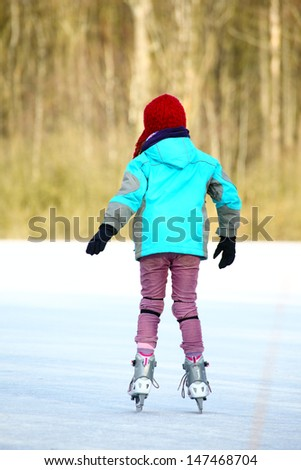 Ice skating girl. Young woman skating on ice with figure skates outdoors in the snow. - stock photo