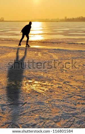 Ice skating - Ice skater at sunset on frozen lake in the Netherlands - stock photo