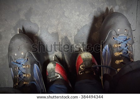 Ice skating in family with shoes of different sizes, symbolizing togetherness. - stock photo