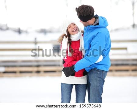 Ice skating romantic couple on date iceskating embracing. Young couple holding hands on ice skates outdoors on open air rink in snowy winter landscape. Multiracial couple, Asian woman, caucasian man - stock photo