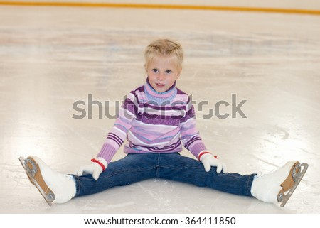 Ice skating. The little girl sitting on ice in ice skating. - stock photo