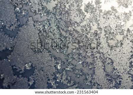 Ice snowflakes and frost pattern with sunlight on Christmas winter frozen window. Colored in gray or silver and blue tone. Selective focus with blur edges of image - stock photo