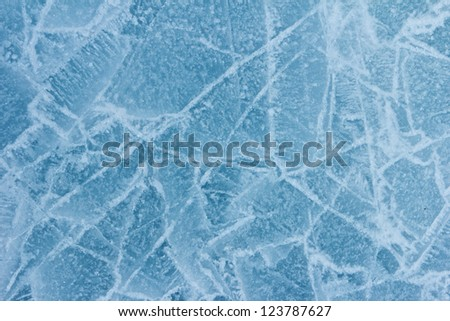 Ice surface of the Baikal water with snow crystals