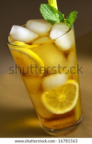 Ice Tea beverage with slices of lemons and garnished with mint leaves. - stock photo