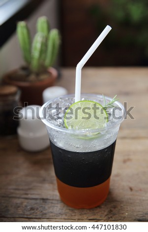 Ice tea with honey and lemon on wooden table - stock photo