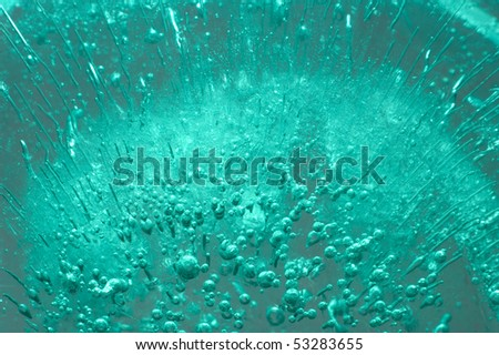 Ice with bubbles of air abstract light green blue macro background texture