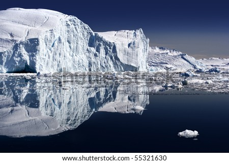 Iceberg and its reflexion in still water - stock photo
