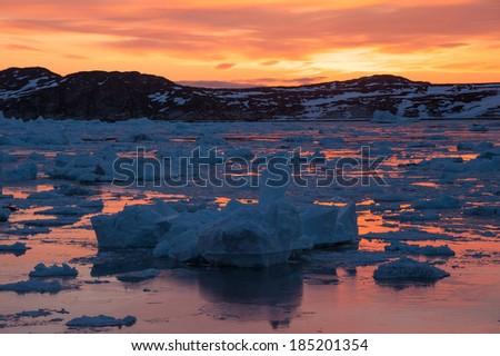 Iceberg and Midnight sun light in Ilulissat, Greenland - stock photo