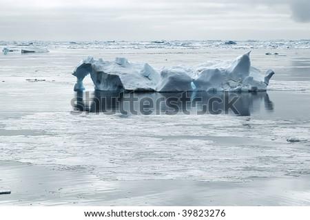 Iceberg drifting in calm waters - stock photo