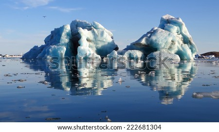 iceberg floating close to a glacier in Iceland - stock photo