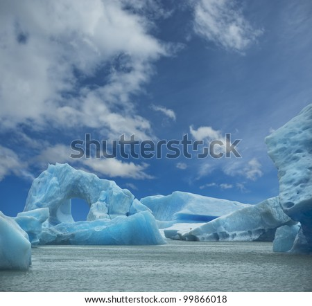 Iceberg floating in the water forming an arch. El Calafate, Argentina. - stock photo