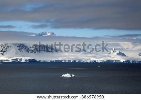 Iceberg in Antarctica with an Adelie Penguin passenger (Hope Bay, Antarctica) - stock photo