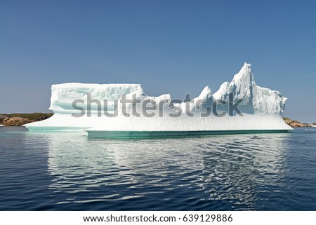 Iceberg in front of a rocky island in Newfoundland and Labrador, Canada
