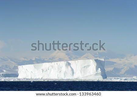 Iceberg in front of coast Antarctica. - stock photo