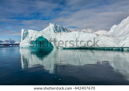 Iceberg in Greenland. No two icebergs are alike, and when you see an iceberg for the first time, you may be seeing shapes and sizes that no-one has seen before.  This one has a cave. - stock photo