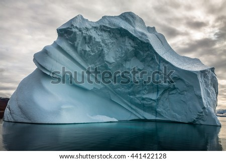 Iceberg in Greenland. The Greenlandic ice cap is in a constant state of change and movement, and every year it produces thousands of icebergs that are primarily formed in the sea from glaciers. - stock photo