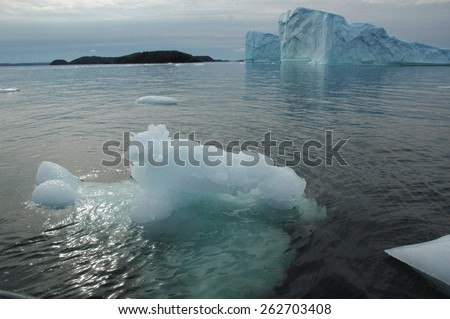 Iceberg in Newfoundland with small icebergs in foreground - stock photo