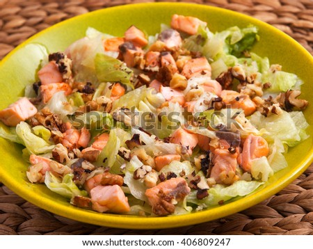 Iceberg salad with baked salmon flakes and crushed walnuts/pecans. Horizontal shot