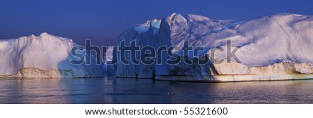 Iceberg wall seen from a little distance. Sunset. - stock photo
