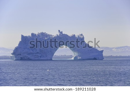 Iceberg with an arch floating in Disko Bay. These icebergs are calved by the Jakobshavn glacier, and usually float North with the currents, eventually turning south and down into the Atlantic - stock photo