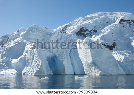 Iceberg with cave and mountain behind it, Antarctic - stock photo
