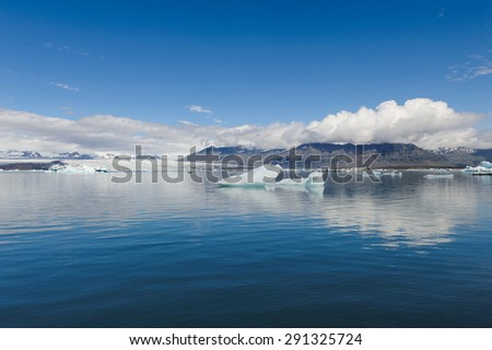 Icebergs floating in blue waters of glacier lagoon on a sunny day, Jokulsarlon in South Iceland