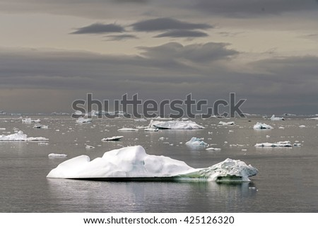 Icebergs in the arctic sea. You can easily see that 1/10th of an iceberg is over the water surface, and 9/10th is below the water surface. Sometimes unbelievable that 90% of an iceberg is under water - stock photo