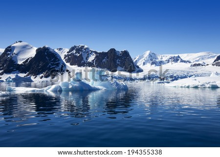 Icebergs of polar regions. Research of effect of global warming on a scientific vessel. Colonies of penguins and sea mammals. - stock photo