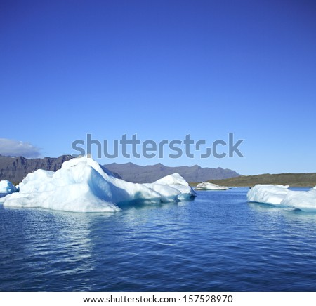 Icebergs on Jokulsarlon lagoon, Iceland against the mountains - stock photo