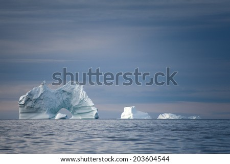 Icebergs with hole in Disko Bay, Ilulissat, Greenland - stock photo